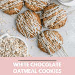 White chocolate oatmeal cookies topped with cream cheese glazes displayed on a gray background.