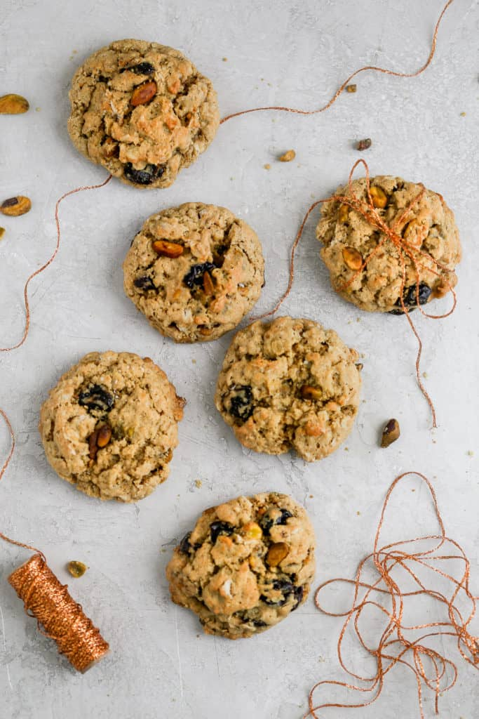 Cherry pistachio oatmeal cookies tied up with string displayed on a gray background