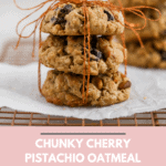 Chunky cherry pistachio oatmeal cookies tied up with string displayed on a cookie rack.