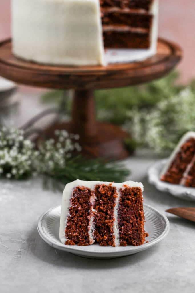 A slice of homemade red velvet cake on a gray plate with the larger cake in the background on a gray backdrop.