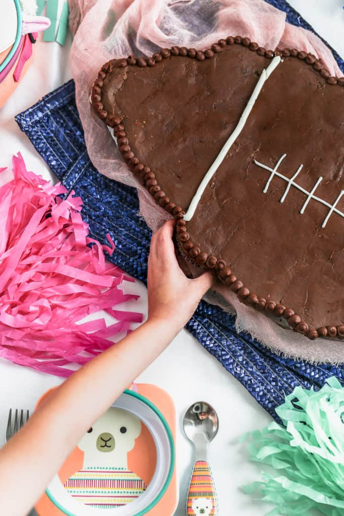 child reaching to pull a cupcake from a football cupcake cake