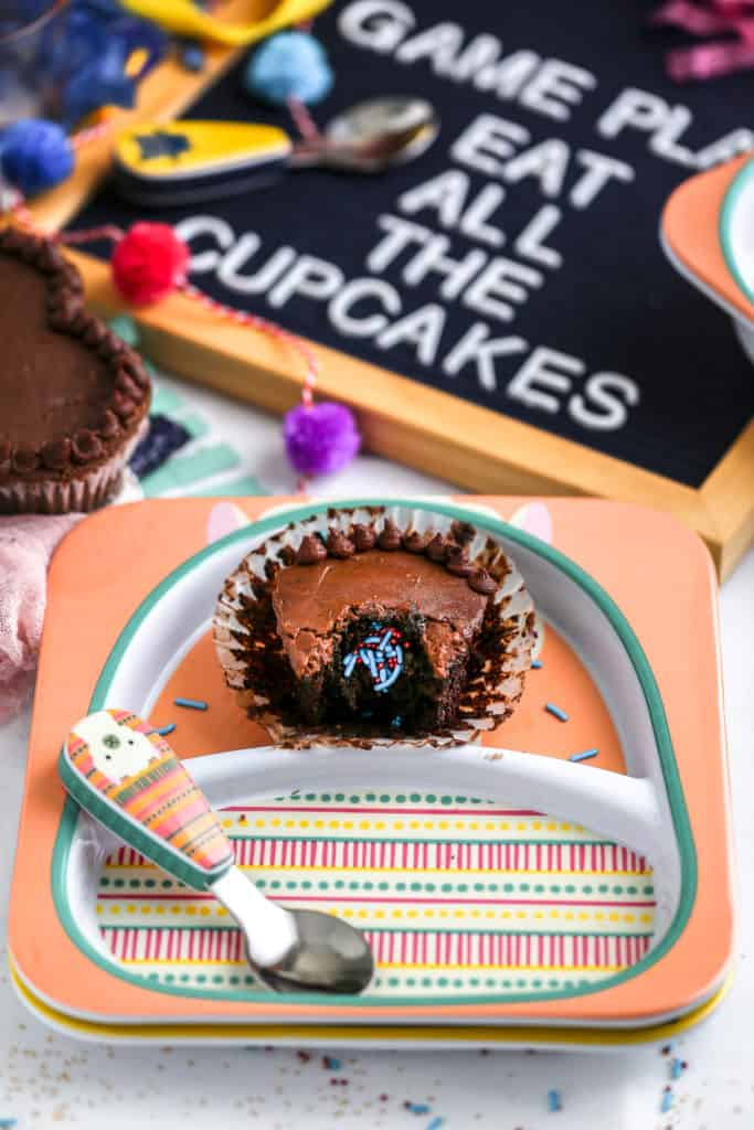 A chocolate cupcake with a sprinkle surprise inside styled on plates from Skip Hop for a football party.