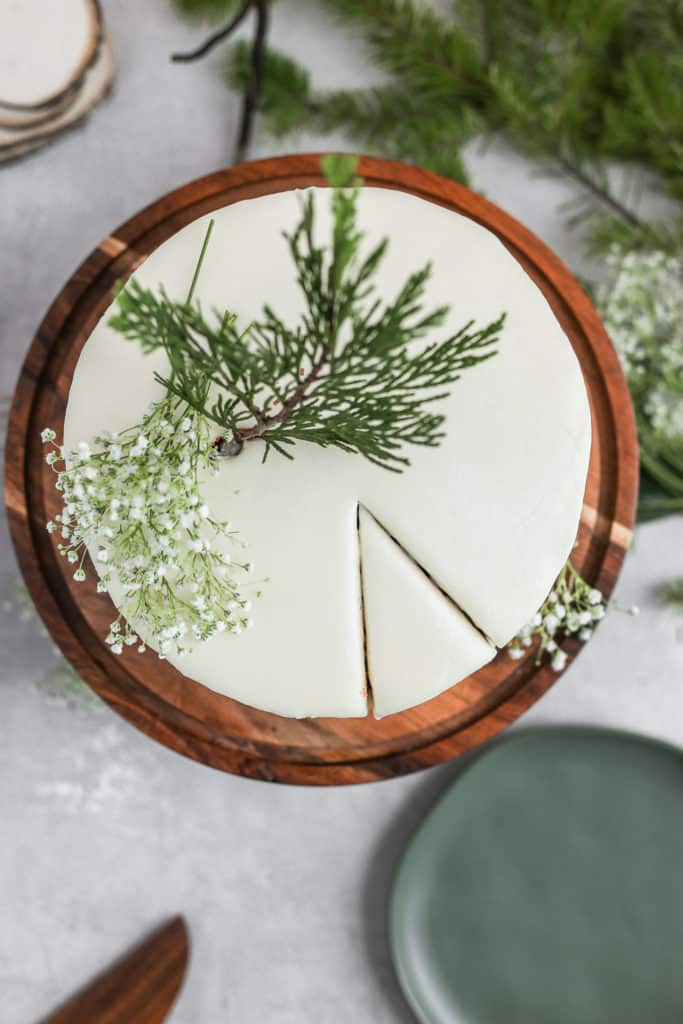 Cream cheese frosted easy red velvet cake decorated with leaves on a wood cake stand on a gray background.