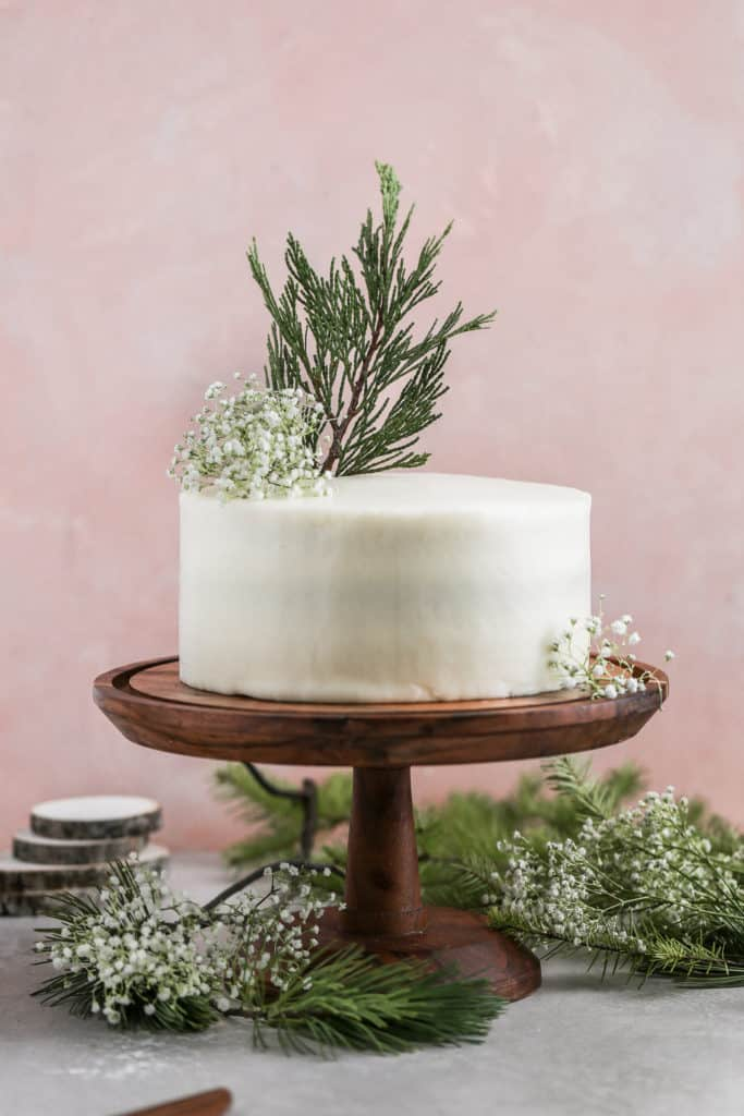 Cream cheese frosted red velvet cake decorated with leaves on a wood cake stand on a pink background.
