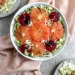 A citrus cabbage salad with grapefruit, blood oranges, cabbage, avocado, and sunflower seeds in a white bowl styled on a pink napkin on a gray surface.