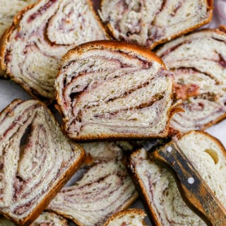 A slice of raspberry cheese babka lying on other slices of babka