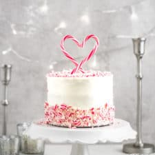 A candy cane peppermint cake with white chocolate peppermint buttercream and a candy cake cake topper styled on a gray background.