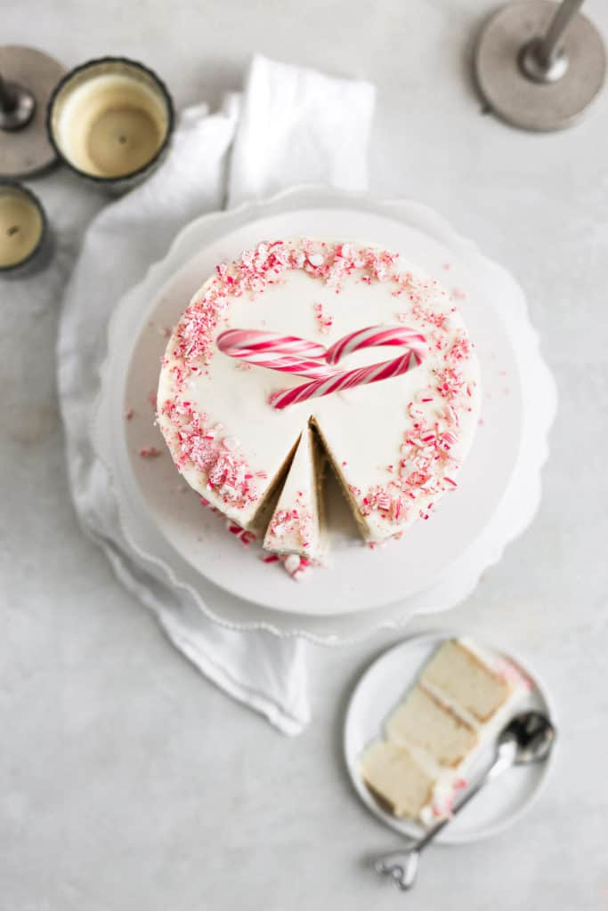 A slice of cake taken out of a peppermint cake styled on a gray background