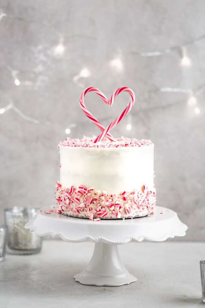 A peppermint cake with white chocolate peppermint buttercream and a candy cake cake topper styled on a gray background.