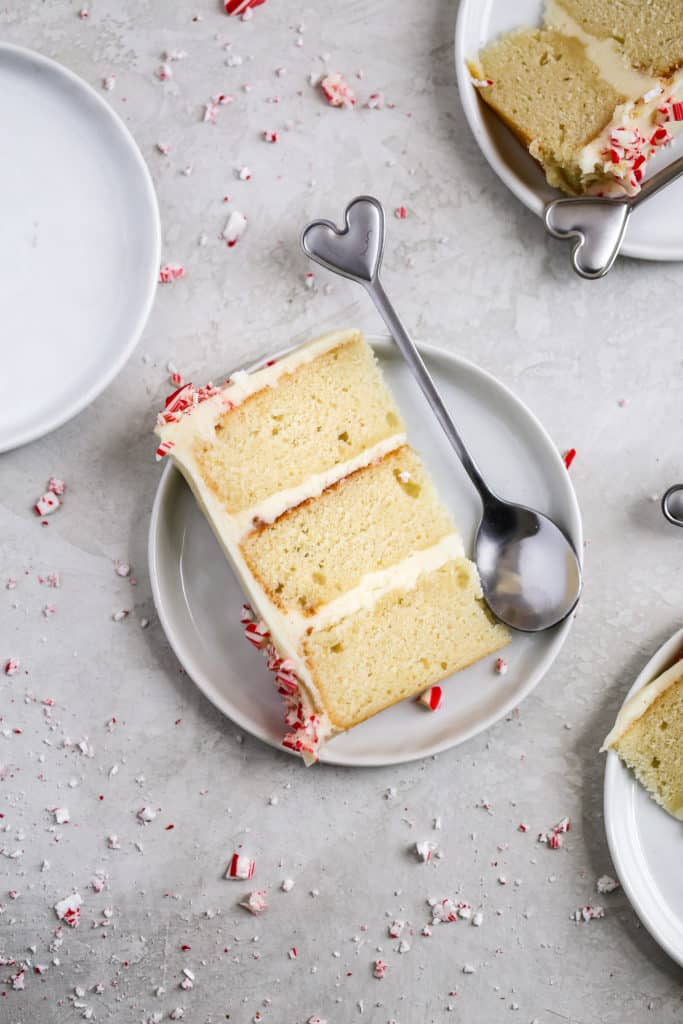 A slice of peppermint cake with white chocolate peppermint buttercream styled on a small plate with a heart shaped spoon on a gray background.