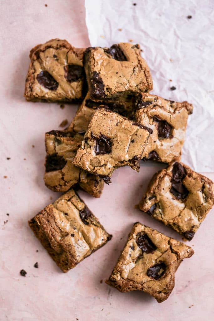 coffee chocolate chip blondie bars on a pink background.