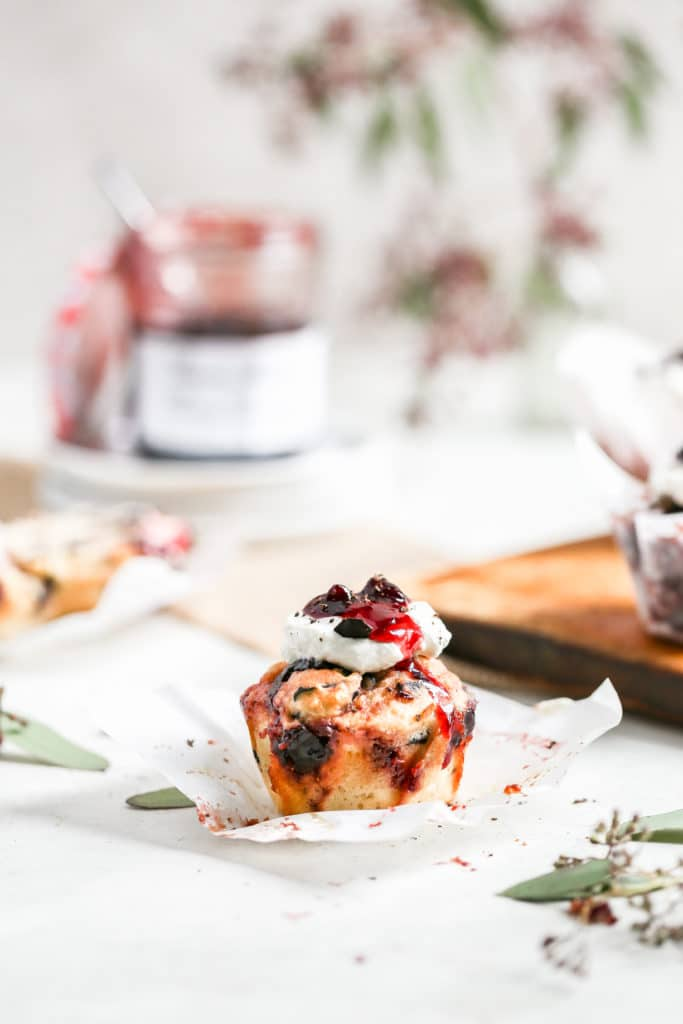Cherry muffin sitting on a stack of white plates with an open can of jelly in the background.