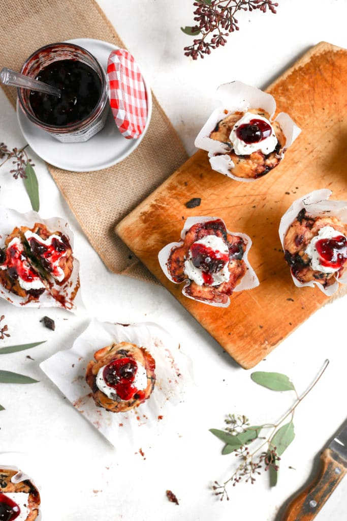 Cherry muffins with whipped cream on a cutting board.