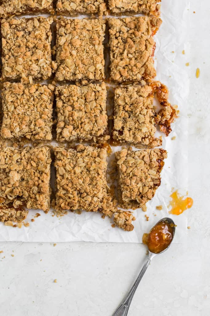 Apricot bars cut into 9 slices on a piece of parchment paper