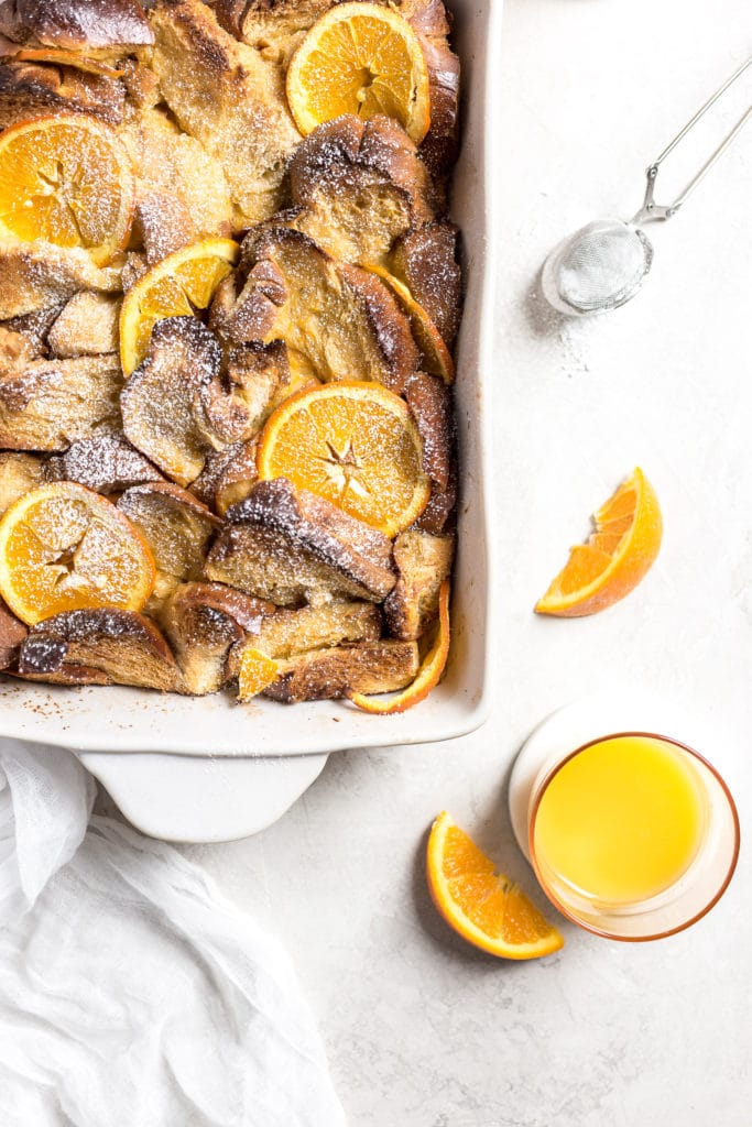 Confectioners sugar topped challah French toast casserole with orange juice on the side.