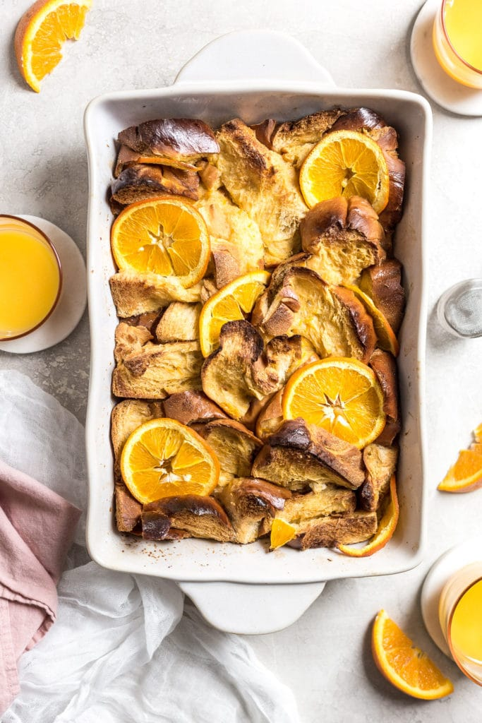 challah pieces in a large dish with orange slices on top