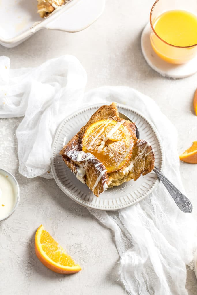 A serving of challah French toast with and orange on top on a plate with orange juice in a cup in the background