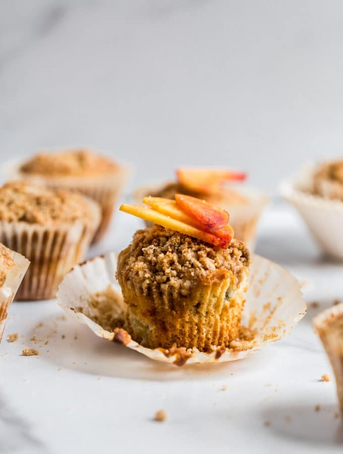 A peach muffin with crumb topping unwrapped from its liner.