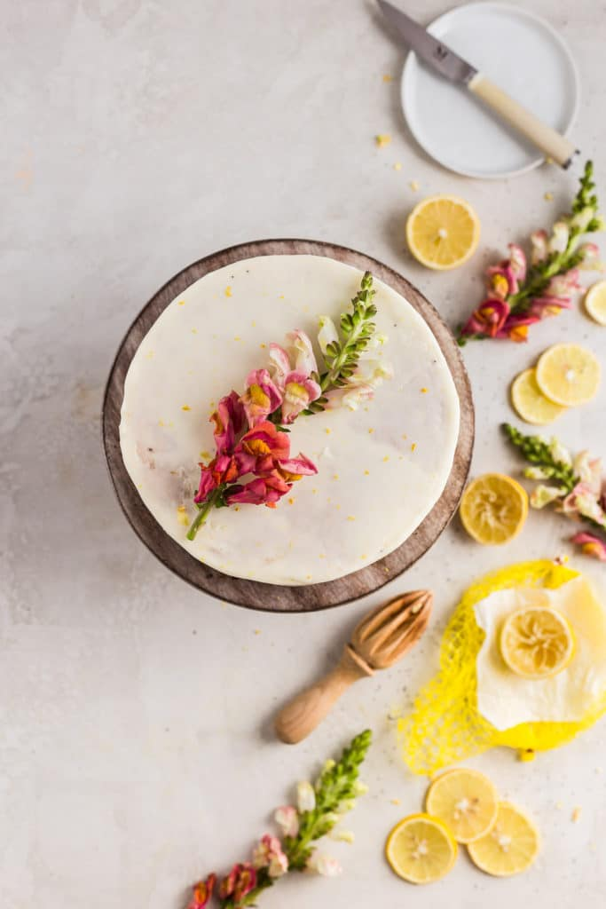 pink flowers on a white cake with lemon slices on the table