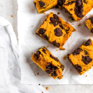 Pumpkin bars with chocolate chunks laid out on parchment paper