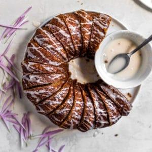 A sliced bundt cake with white glaze drizzled nex to the bowl of glaze.