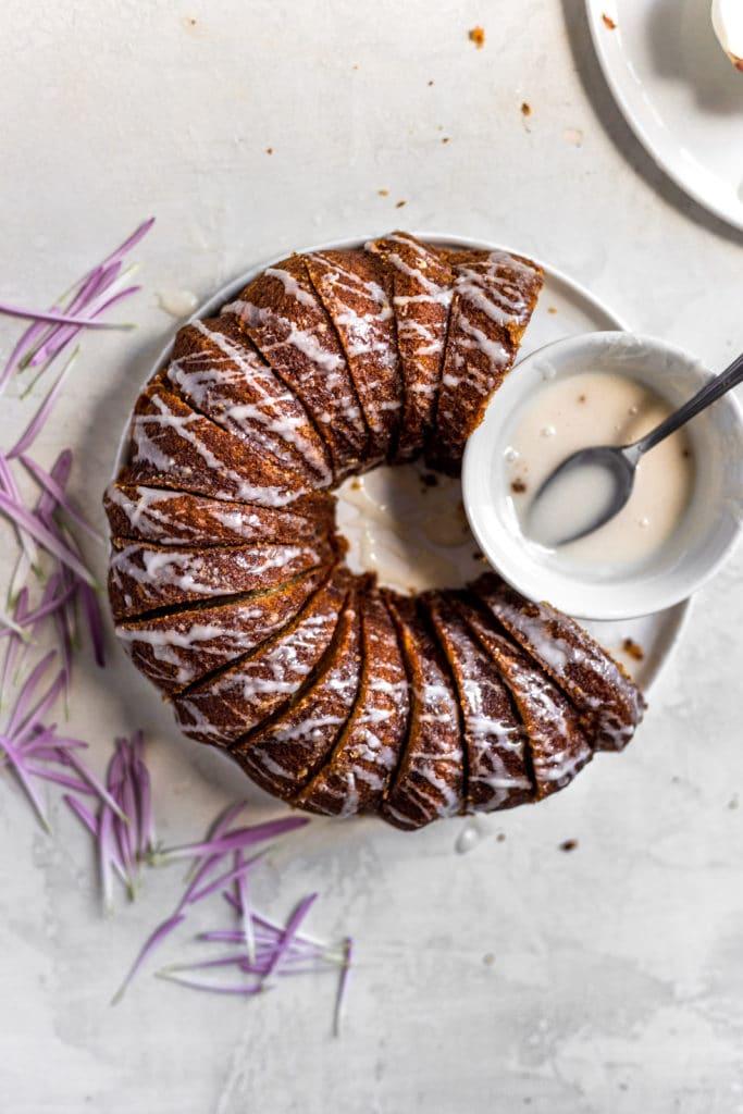 Apple bundt cake with white glaze drizzled next to the bowl of glaze.
