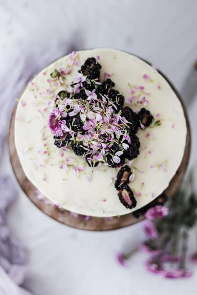 The top of a white cake with blackberries and flowers.