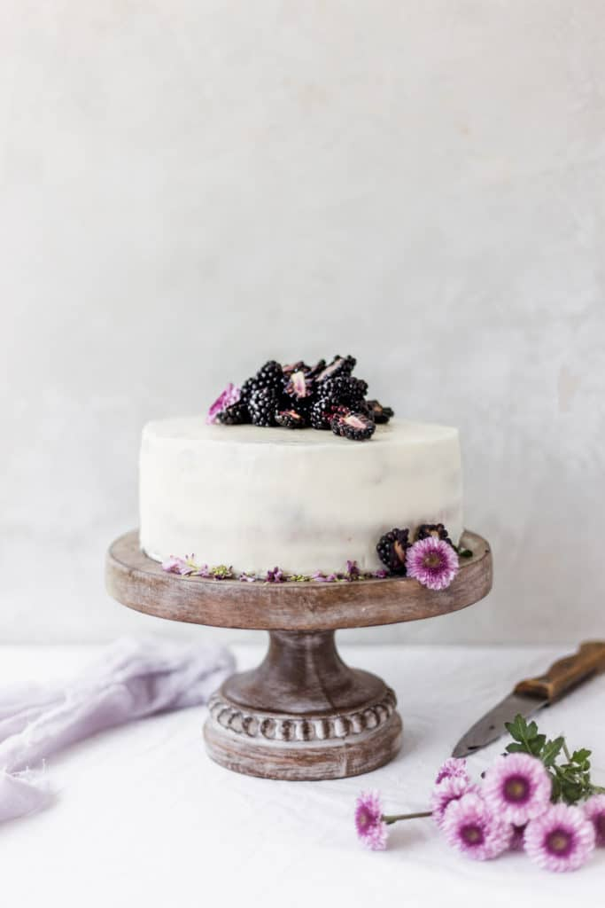 White cake on a brown cake stand with purple flowers and blackberries