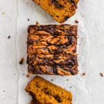 Slices of pumpkin bread with chocolate lined up on a white surface.