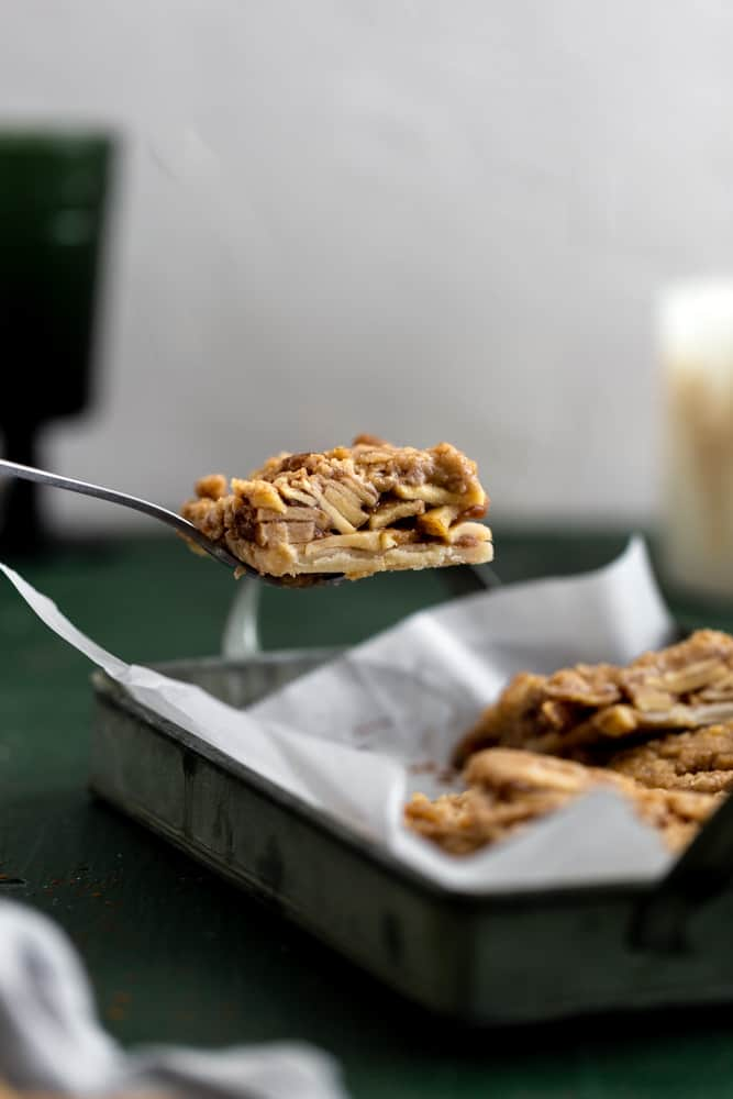 apple pie bar lifted out of a pan with a spatula