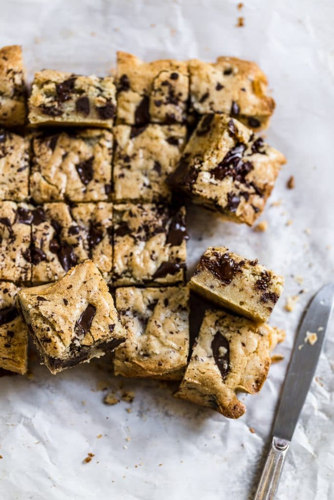 Blondies with chocolate chips cut up and put on its side to show you the melty chocolate inside.