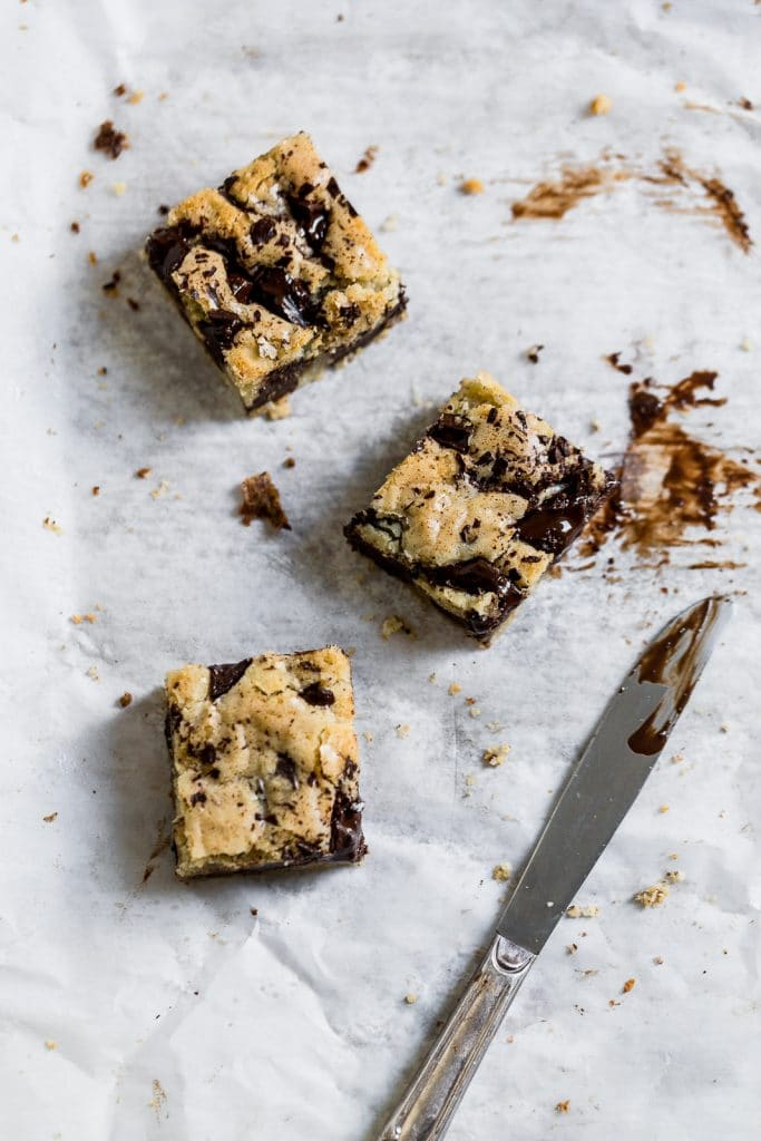 3 chocolate chip blondies arranged with a knife on a white surface