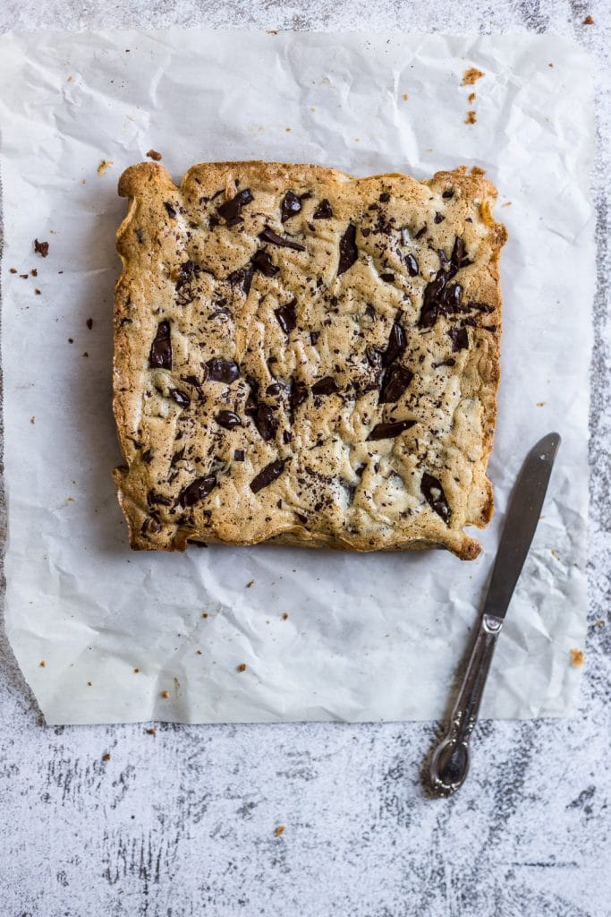 Fully baked chocolate chip blondies in one square on parchment paper
