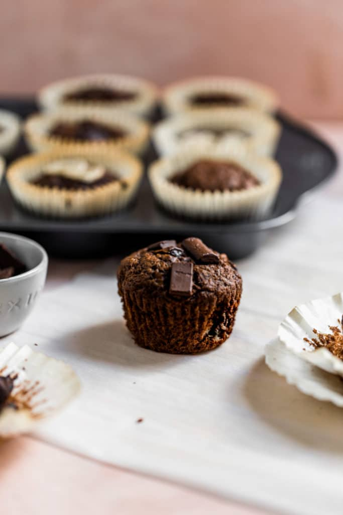 A chocolate muffin on a white surface with a muffin tin full of muffins in the background.