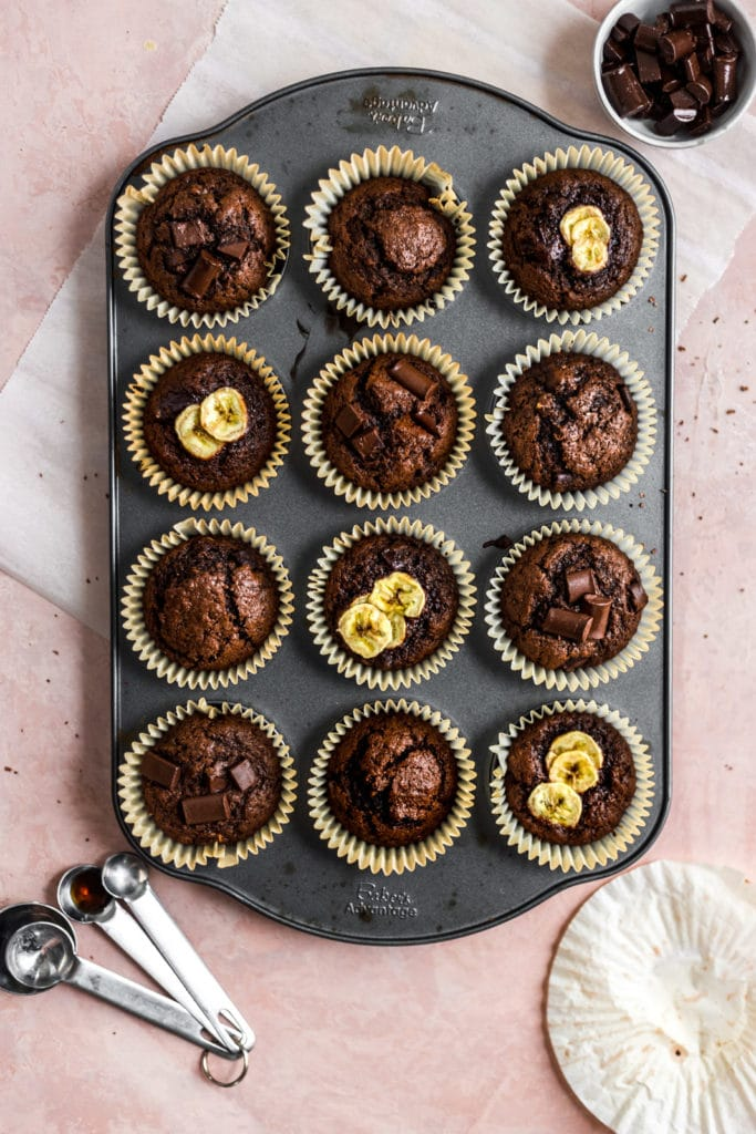chocolate muffins in a muffin tin topped with chocolate and sliced bananas.