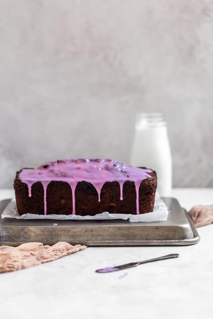 Side view of banana bread with purple glaze dipping down.