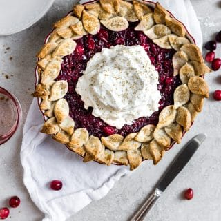 Cranberry pie with whipped cream resting on a white linen on a gray backdrop with a knife lying on an angle.