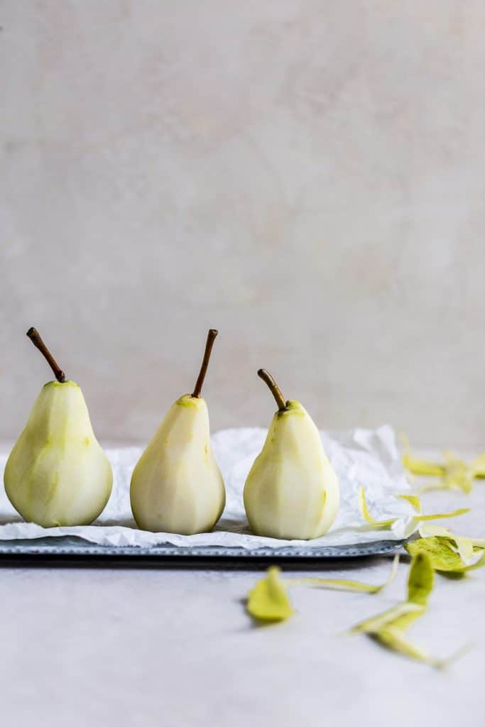 3 peeled pears on a tray with parchment paper