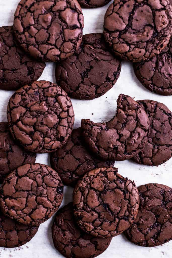 Brownie cookies on a white surface with one taken a bite out of it.