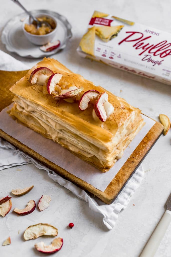 A Napoleon dessert made with phyllo dough on a wooden cutting board topped with dried apples.