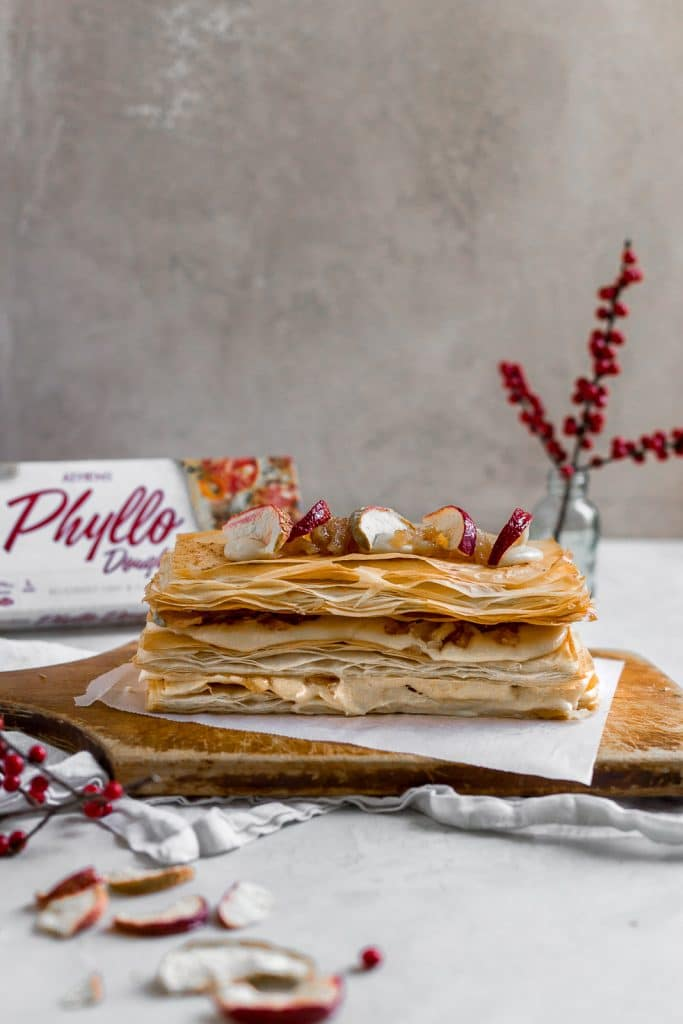 A Napoleon dessert made with phyllo dough on a wooden cutting board topped with dried apples and red flower berries in the background.