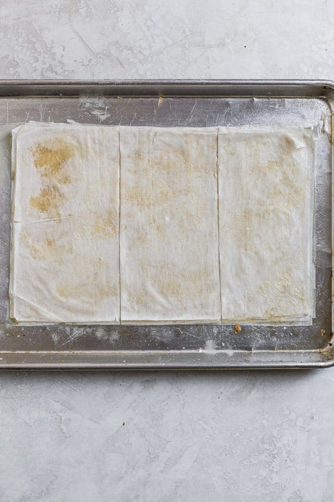 Phyllo dough layers brushed with butter and cut into thirds on a baking tray.