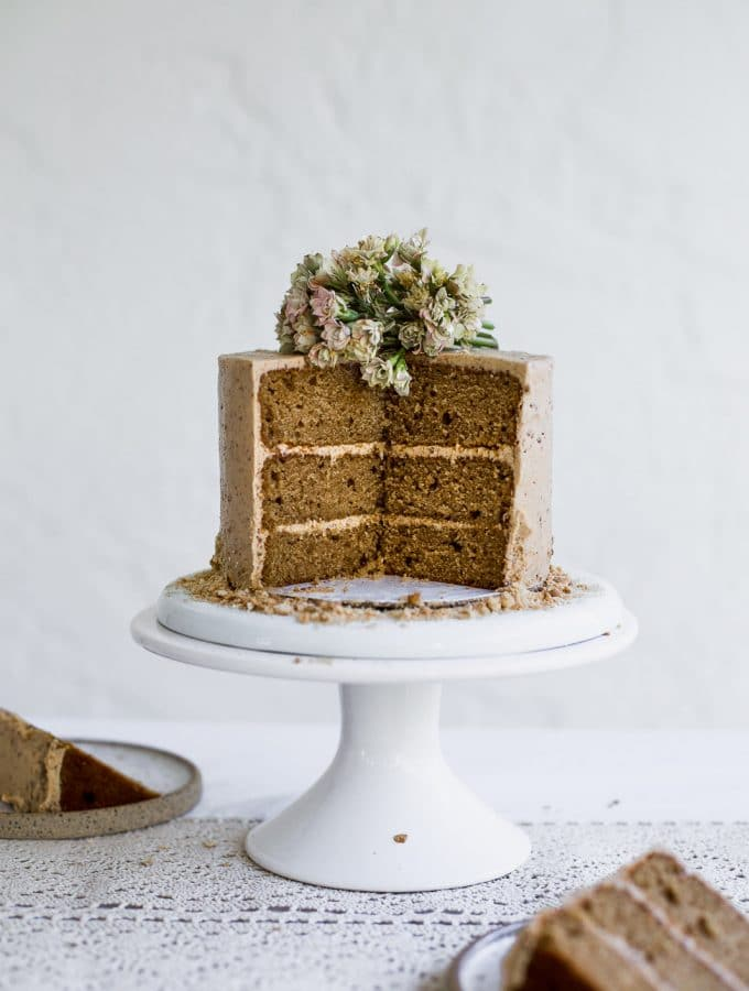 A brown cake with beige frosting that has a few slices taken out of it sitting on a white cake stand on a white background
