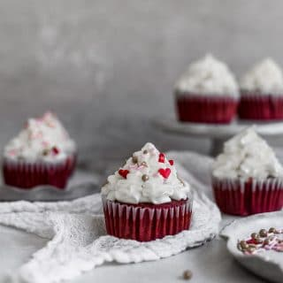 a red velvet cupcake with cream cheese frosting sitting on white gauze with other cupcakes in the background on a gray surface.
