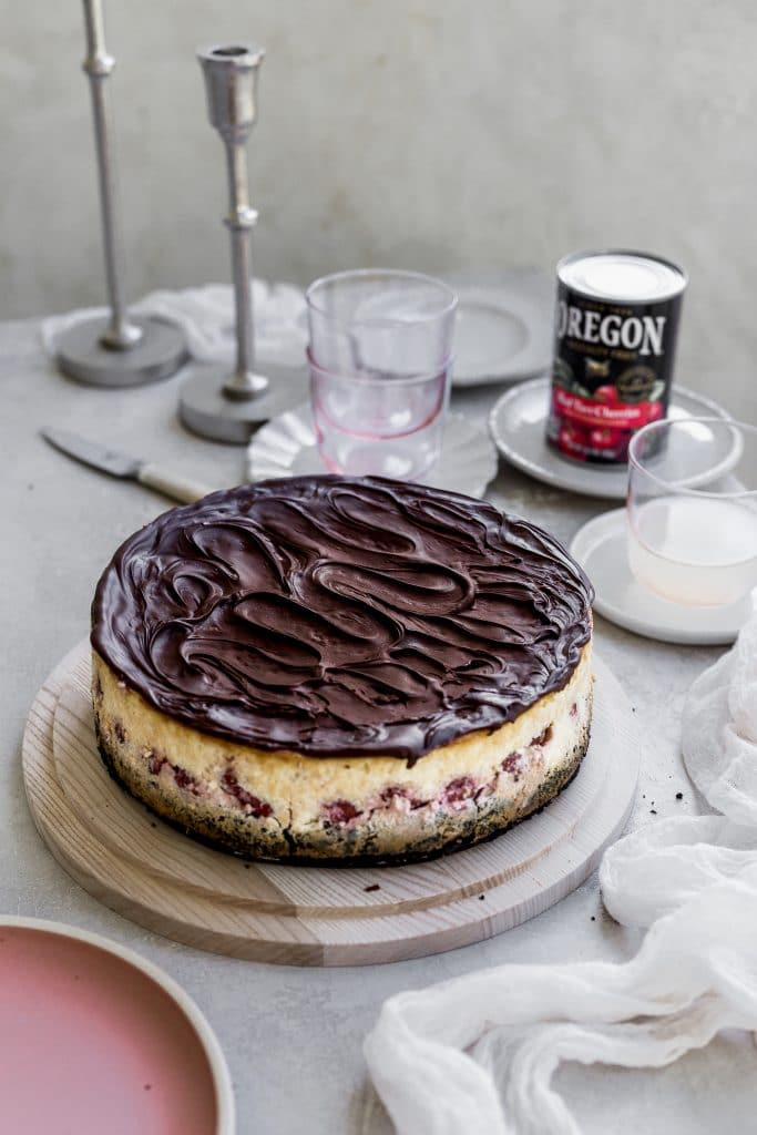 A chocolate topped swirled cheesecake sitting on a wooden cake plate on a gray table with plates and cups to the right side of it and a can of Oregon fruit red tart cherries set in the back on a plate.