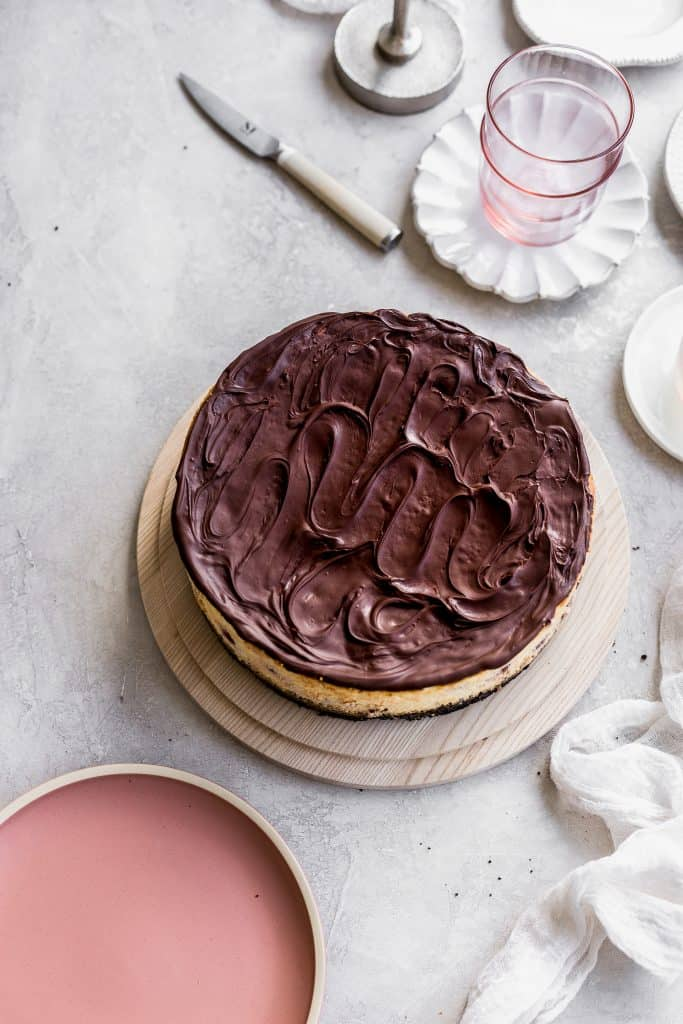 Chocolate swirled all over the top os a cheesecake on a wood cake plate on a gray background with pink plates around it.