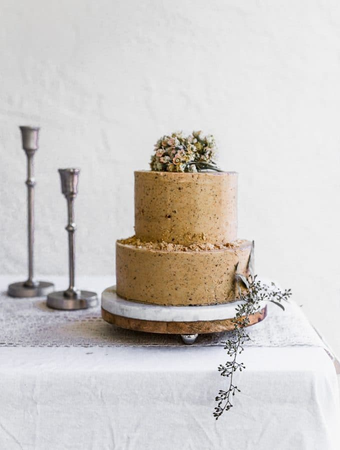 A two tier cake with light brown frosting sitting on a marble cake stand on a white table with candlesticks in the background
