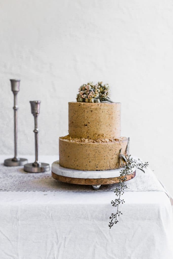 A two tier brown cake decorated with flowers and cookie crumbs sitting on a white table with silver candlesticks in the back