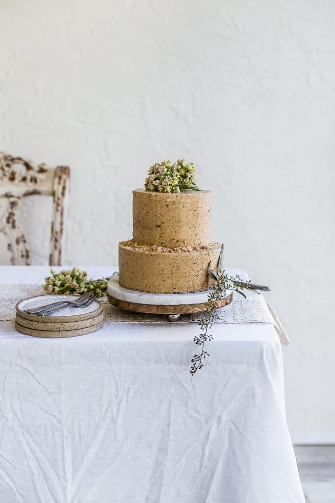A two tier brown cake decorated with flowers and cookie crumbs sitting on a white table with plates and forks on the side.