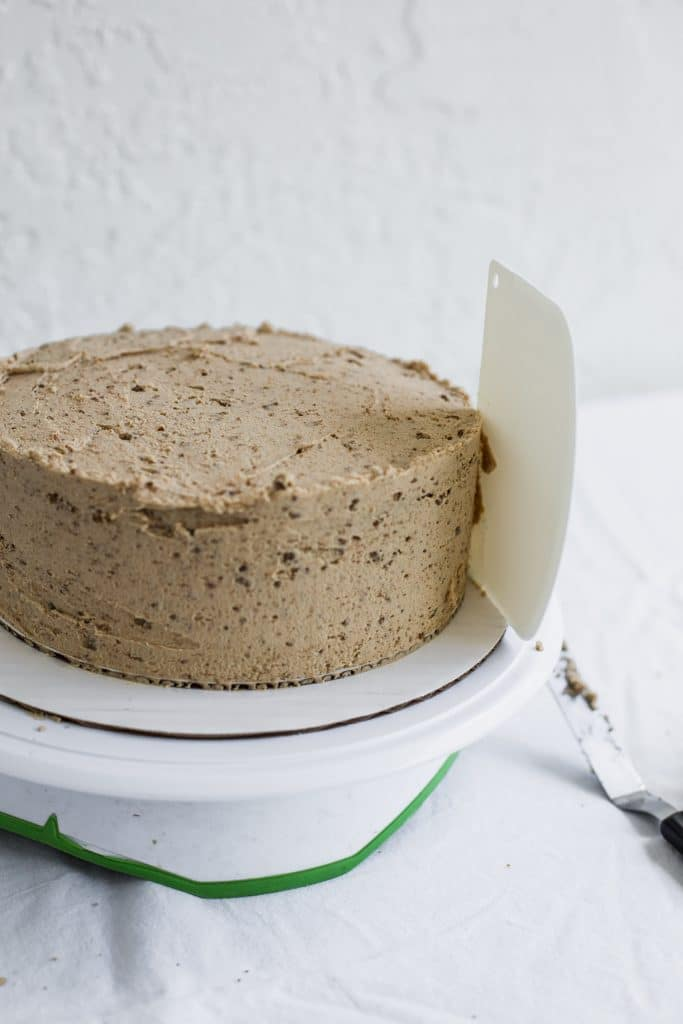 A white bench scraper sticking to the side of a beige frosted cake